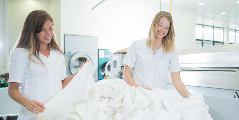 Textilversorgung - Wäscheversorgung durch 2 Frauen mit Arbeitsbekleidung in einer Wäscherei beim Zusammenlegen und Reinigen von Textilien